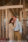 New home construction stock photo of  a happy hispanic couple embracing and smiling at the site of the new home being built for them.